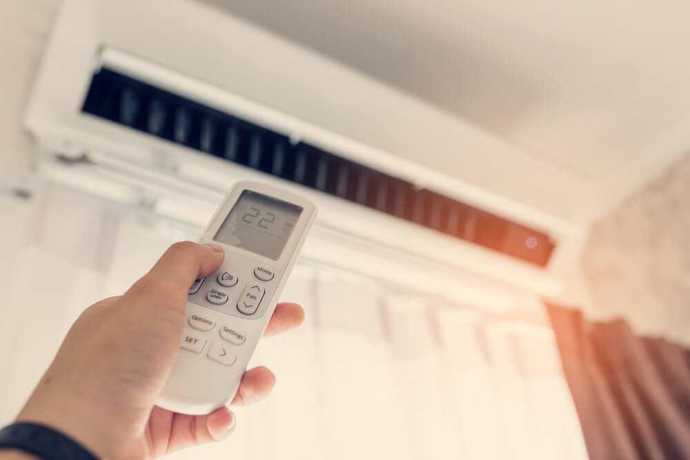 Air Conditioner Inside the Room With Woman Operating Remote Controller.