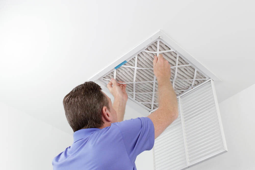 Caucasian Male Removing a Square Pleated Dirty Air Filter With Both Hands From a Ceiling Duct.