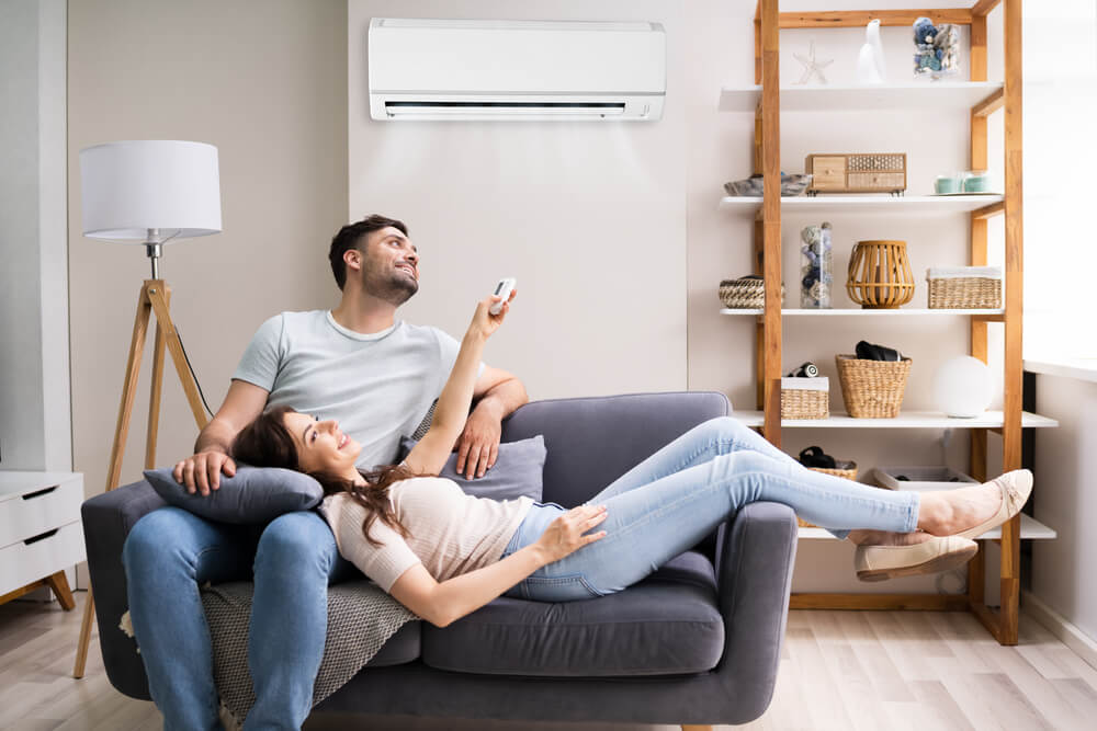 Happy Woman on Bed Holding Air Conditioner Remote Control