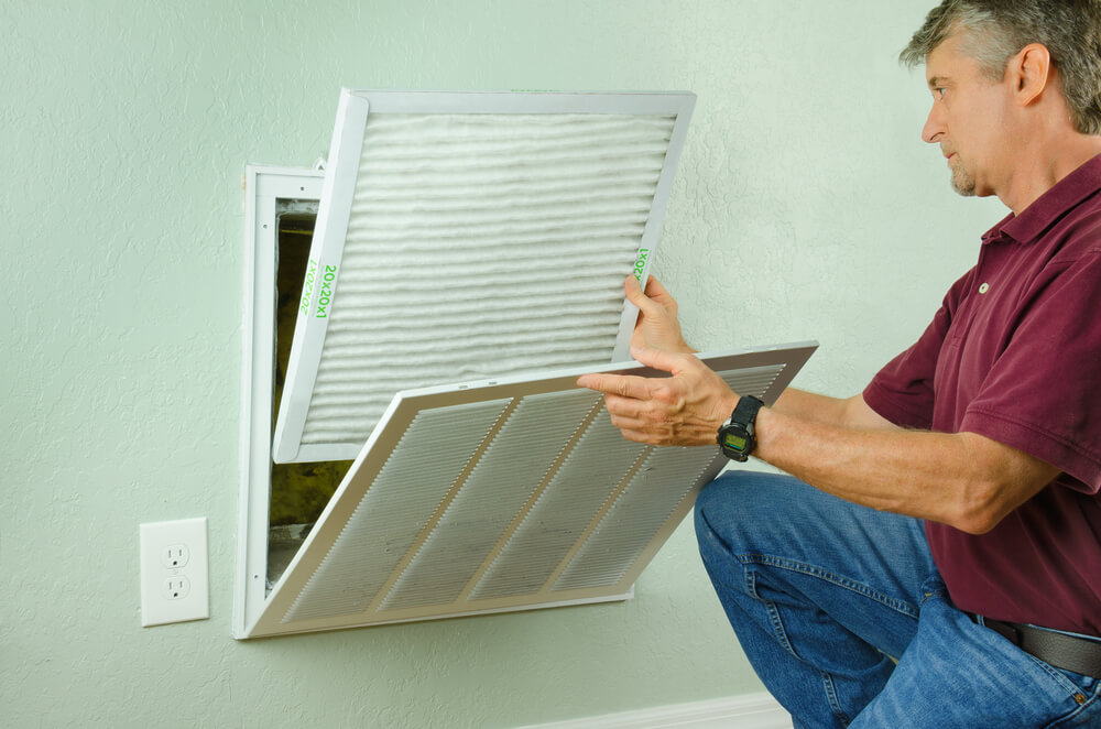 Professional Repair Service Man or DIY Home Owner Installing a Clean New Air Filter on a House Air Conditioner